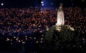 A statue of Our Lady of Fatima is carried through the crowd May 12 at the Marian shrine of Fatima in central Portugal. Thousands of pilgrims arrived at the shrine to attend the 99th anniversary of the first apparition of Mary to three shepherd children. Lucia dos Santos and her cousins, Francisco and Jacinta Marto, received the first of several visions May 13, 1917. (CNS photo/Rafael Marchante, Reuters)